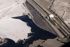 An oil sands facility is seen from a helicopter near Fort McMurray, Alta., Tuesday, July 10, 2012. The federal government's first line of defence against critics of the oilsands was to be a revamped environmental monitoring system, unveiled with fanfare in Alberta in February last year.But the three-year plan to keep a closer watch on the air, water and habitat in northern Alberta has still produced no formal results. THE CANADIAN PRESS/Jeff McIntosh