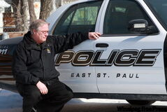 Jerome Mauws squats next to a police car his community is still stuck with after the local service was disbanded and replaced with an RCMP detachment. At least one former officer says his life was left in ruins because of his association with the former police department.