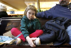Bronwyn Smyth, 7, sits next to her dad at Grant Park Shopping Centre Monday after waiting hours for flu shots to arrive.