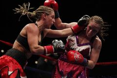 Winnipeg's Olivia Gerula (left) batters challenger Brooke Dierdorff Millbrook during their WBC female super featherweight title fight Thursday night.