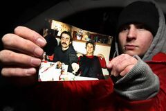Chris Bozynski holds a photo of his father Zenon and his mother Heather, days after his father was killed in 2011.