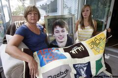 Donna and (right) Kara Twomey, mother and sister of drug overdose victim Derek Twomey, 21, hold a picture of Derek and a quilt made from his T-shirts.