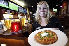 Kyanne MacDonald-Johnson, manager of Cityplace Boston Pizza, shows product.