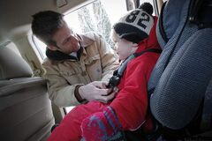 Winnipegger Tom Wallace buckles son Soren into his car seat Friday. New rules that come into  effect  tomorrow  are intended to help make child seats safer.