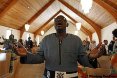 Rev. Joseph Seidu sings and sways during services at Crestview Park Free Methodist  on a recent Sunday. Lindor Reynolds visited the small St. James house of worship that is  home to many newcomers.
