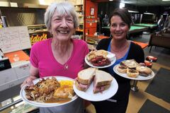 Annette Gougeon and Tanis Desrochers hold liver special, corned-beef sandwich, perogy platter, butter tart at Eddy's Place on Selkirk Avenue.