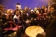 People huddle in the rain as drummers play at a vigil for missing and murdered women at the legislative building in early October.