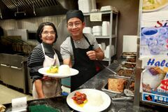 Lourdes Velasco (part owner) and head chef  Dye Castro dish out food.