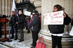 Lake St. Martin First Nations' resident  Maryjane Beardy  holds a sign while Chief Adrian Sinclair speaks during rally.