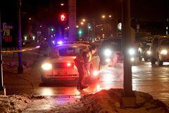 A police officer re-ignites his flares at the corner of Century Street and Sargent Avenue Thursday evening where a crash involving two pedestrians forced the closure of Century St.