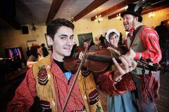 Festival du Voyageur performer Michael Audette plays a polka on his fiddle while members of the official Festival family do a quick dance during the progrmming announcement at Fort Gibraltar.