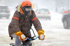 A cyclist wearing goggles makes his way north down Memorial Boulevard against a nasty winter wind on a cold day in Winnipeg Saturday morning.