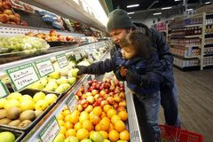 Andrew Guimond and son Aiden, 4, pick up fresh produce  at the First Nation's new Superstore.