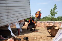 Environment Canada personnel take the measurements of a home a tornado ripped off its foundation in Sioux Valley Dakota Nation.