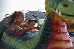 Siblings Gabriel Daniels, 6, and Akwatin, 2, of Saskatoon take a wild ride atop a dragon roller coaster at the midway of the Manitoba Stampede.