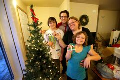 The Van De Kaere family in front of their dressed Christmas tree in their new habitat home in Elmwood.