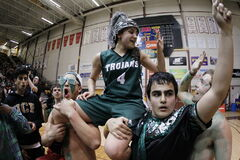 Tournament MVP Atoosa Jalayeri is hoisted after leading the Vincent Massey Trojans to the high school basketball crown.