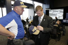 Head coach Mike O'Shea signs a hat for Bomber  alumnus Mike Hameluck Monday at the Bombers Fan Forum.