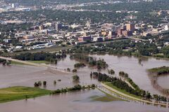 Downtown Brandon is seen in the background behind the flood waters covering 1st Street, Dinsdale Park and the Optimist Park soccer pitches on Saturday morning.