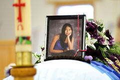 Tina Fontaine's photographs sit on top of her casket surrounded by  flowers and items in the colour purple, her favourite colour, in front of Roman Catholic Church at Sagkeeng First Nation for her funeral.