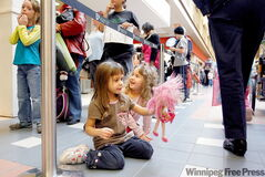 Jenna Haugh and friend Chiara Kirilaht play with dolls while waiting in the long line with their mothers for H1N1 shots at the Grant Park Shopping Centre Monday.