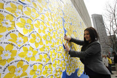 Vanessa Kunderman, a cancer survivor whose father died of cancer, attaches a message on the giant daffodil tribute wall for her  supportive mother Lorraine Shapera last year. This year marks the Canadian Cancer Society's 75th anniversary.