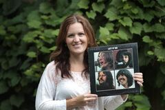 Stacey Nattrass with a copy of Let it Be.