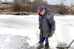 Elder Sam Harper from Wasagamack First Nation retrieves water from Island Lake for his family. More than 1,400 homes on Manitoba reserves have no running water.