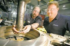 President Richard van den Broek (right), and Neil Leost, a journeyman machinist, set a vertical lathe at Dynamic Machine Shop on Wednesday. Dynamic is expecting to expand its workforce in 2011 following the acquisition of K&S.