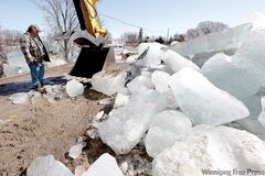Harvey Johnson works with an excavator to clear ice jams on the Icelandic River in Riverton.