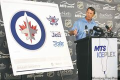 Jets governor Mark Chipman shows off his team's new logos Friday. He says the main symbol reflects Winnipeg's close connection to the nation's air force.