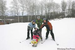 Mary Rollason-MacAulay, with ski instructor Dave Zerr behind her and parents Gail MacAulay and Kevin Rollason on either side, leaves her wheelchair behind to ski down a hill on the resort's sit ski.