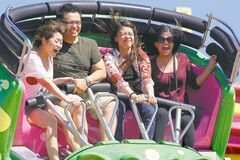 John Woods / Winnipeg Free Press  Amusement riders hold on tight on the Crazy Mouse at the Red River Ex yesterday. Despite poor weather, festival revenues are only off slightly from last year, while attendance numbers are due today.