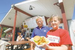Owners Donat and Elaine Mellor pose with their popular burger and fries at  Le Bébé Rouge near St-Pierre-Jolys on Highway 59.