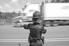 Truck passes Ontario Provincial Police officer in 2004 picture.