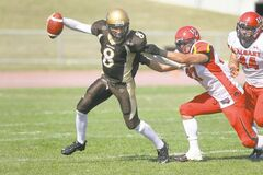 Bisons QB Cam Clark is hauled down by a Dinosaur defender Saturday afternoon at University Stadium.