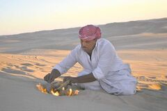 Desert safari driver Ahmed Bakrin building a small bonfire to make mint tea before sunset during a trek through the Great Sand Sea outside the Egyptian oasis of Siwa.