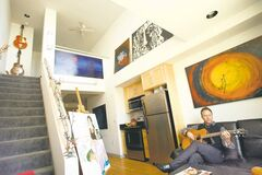 Timm Freeman plays guitar in his 350-square-foot apartment in the Olympic Studios complex in Santa Monica, California.