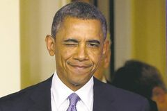 U.S. President Barack Obama winks as he arrives to make a statement regarding the passage of the 'fiscal-cliff' bill.