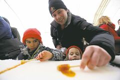 Roger Vermette helps his children Maxime, 6, and Jasmine, 3, get some famous Festival maple syrup taffy.