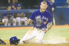 Toronto Blue Jays' Brett Lawrie gets down and dirty at home plate, scoring on a single by Melky Cabrera in Sunday's win over the Yankees.
