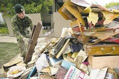 Cpl. Brett Martens from CFB Edmonton helps a resident clear out damaged debris from their home near downtown Calgary on Sunday.