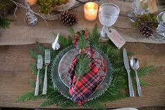 Make your own dinner charger using fresh cedar. Tartan napkins have homemade napkin rings made with rusty bells and a bit of twine.