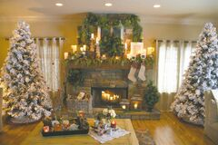 When your family gathers around the fireplace this holiday season, make it special with a bounty of fresh and faux greens on your mantelpiece. Shown: Reallite candles are staggered along the length of Jan and Ralph Regehr's mantle, casting their glow on branches, berries, and pinecones for a natural, eyecatching display.