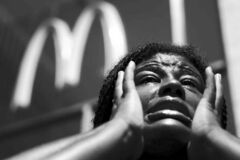 Angela Owens wipes away tears Thursday as she speaks to the media outside a McDonald's in Philadelphia at a protest to push fast-food chains to pay their employees at least $15 an hour.