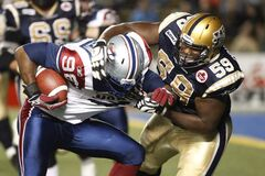 Winnipeg Blue Bombers' Andre Douglas (59) wraps up Montreal Alouettes' Jermaine McElveen (98) in a 2011 game. Douglas, who was considering making a move tot he NFL, has re-signed with the Bombers.