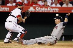 Cleveland Indians' Lonnie Chisenhall (8) scores on a sacrifice fly by Michael Brantley, as the throw is offline to Los Angeles Angels catcher Chris Iannetta during the seventh inning of a baseball game Tuesday, April 29, 2014, in Anaheim, Calif. (AP Photo/Alex Gallardo)