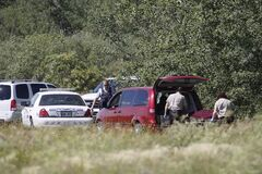 RCMP remove a body from a wooded area off Highway 4, just north of Selkirk, on Sunday.