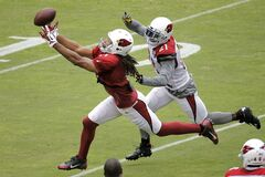 Arizona Cardinals' Larry Fitzgerald, left, reaches for the pass as Patrick Peterson defends during football camp practice, Monday, Aug. 18, 2014, in Glendale, Ariz. (AP Photo/Matt York)