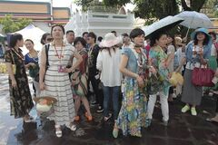 A group of Chinese tourists take a shelter in the shade while touring Wat Pho in Bangkok, Thailand Tuesday, May 27, 2014. The drama of Thailand's military takeover has played out mainly in the political arena. While the army detains political leaders and issues stern warnings on TV, tourists are kicking back on the country's famed beaches and sightseeing in Bangkok. The main impact on visitors for now is a 10 p.m. curfew, which forces nightlife to close four hours earlier. (AP Photo/Sakchai Lalit)